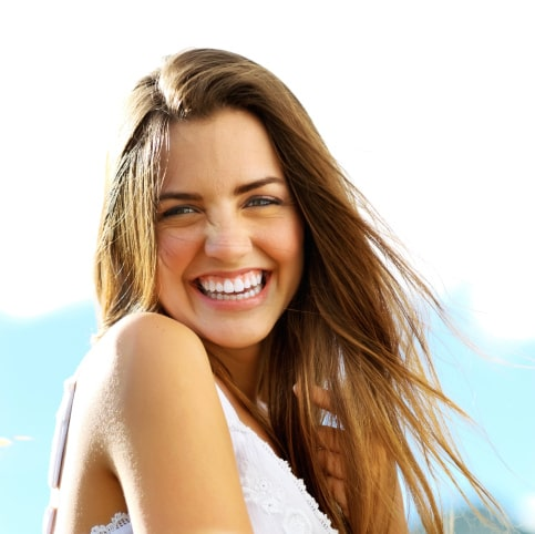 A smiling woman illustrates how dental implants from our Beaverton dentist can restore your smile