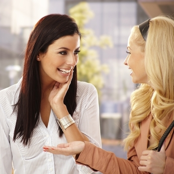 Two business women talking and smiling