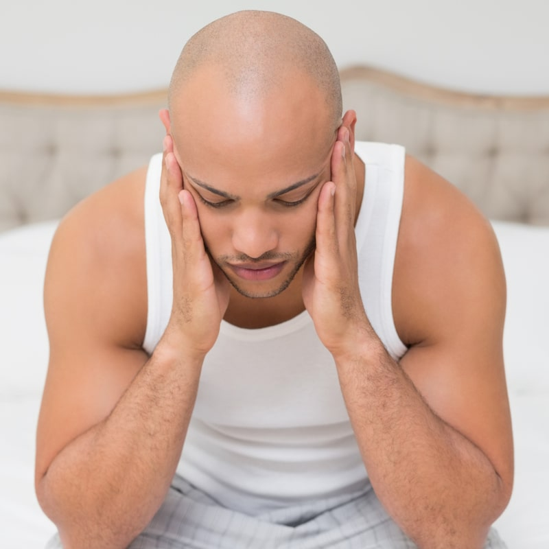 A man holding his head illustrates how TMJ pain can be treated by our dentists in Beaverton, OR.