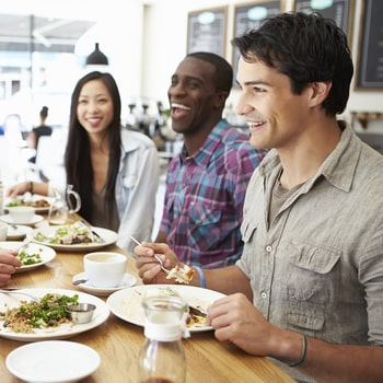 A group of friends dining out at a modern restaurant to show that Beaverton dental implants allow you to eat normally.