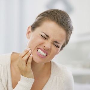 A woman holding her jaw to illustrate how TMJ pain can be treated with our Beaverton family dentistry services.