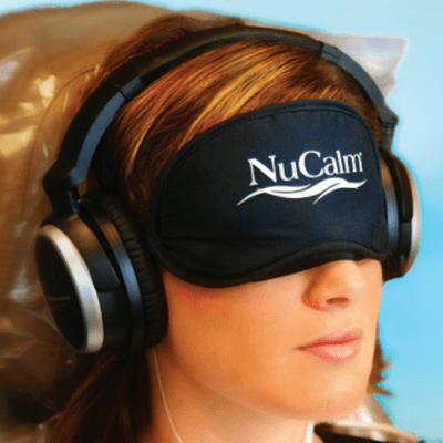 A woman wearing a sleep mask illustrates how we use NuCalm to help patients with dental anxiety.