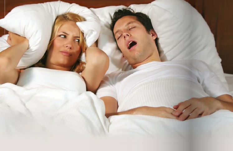 A woman covering her ears with a pillow while her husband snores